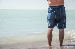 man standing on beach on holiday on sunny summer day with blue s royalty free stock images