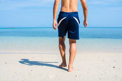 Man with no shirt walking barefoot. On white sand beach into the sea Stock Photos