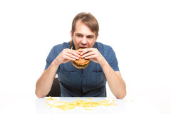 Man is not careful eating tasteless burger. Drops potatoes Royalty Free Stock Image