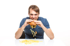 Man is not careful eating tasteless burger Stock Images