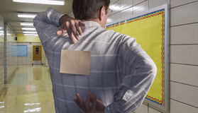 Man with note on back in school hallway Royalty Free Stock Photography