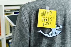 Man with a note with the text happy fools day attached to his ba. Closeup of a young man with a paper fish and a note with the text happy fools day attached with royalty free stock images