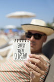 Man with a note with the text sorry we are closed. Closeup of a young man wearing sunglasses and straw hat relaxing in a sunlounger in the beach showing a spiral Stock Images