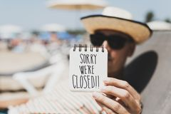 Man with a note with the text sorry we are closed. Closeup of a young man wearing sunglasses and straw hat relaxing in a sunlounger in the beach showing a spiral Royalty Free Stock Photo