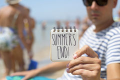 Man with a note with the text summers end. Closeup of a young man in the beach showing a spiral notepad with the text summers end handwritten in it Stock Photo