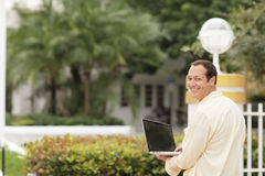 Man with a notebook computer smiling Stock Photos
