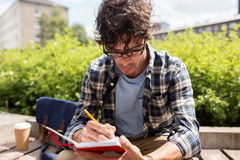 Man with notebook or diary writing on city street Stock Photo