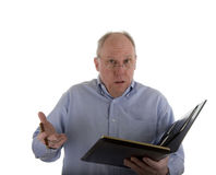 Man With Notebook Explaining Problem. A man in a blue shirt with a pen and a notebook, giving an explanation or an excuse Stock Image