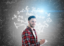 Man with notebook and formulas on board Stock Images