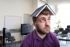 Man with notebook on his head Royalty Free Stock Image