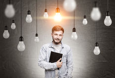 Man with notebook and many light bulbs Royalty Free Stock Photography