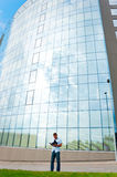 Man with notebook and mobile phone in front of modern business building Royalty Free Stock Photo