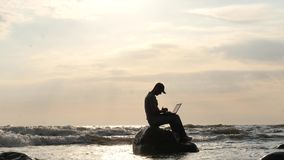 Man with notebook on rock in the stormy sea finishing type dolly shot stock video footage