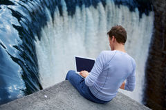 Man + notebook sitting over the waterfall