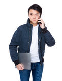Man with notebook and talk to cellphone Stock Photo