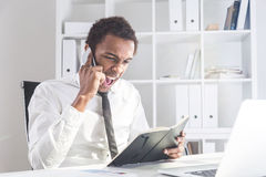 Man with notepad shouting. Furious african american businessman sitting at office desk with notepad in hand and shouting at interlocutor over the phone. Concept Stock Images