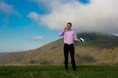 Man with notepad and telephone on mountain Stock Images