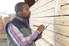 Man noting references from stack wood. Man noting references from stack of wood Stock Photo