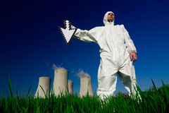 Man at nuclear plant. Man in white protective jumpsuit holds an arrow pointed downwards in front of a nuclear power plant Royalty Free Stock Photos