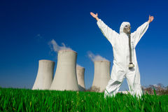 Man at nuclear power plant. Man wearing protective suit and gas mask standing in front of nuclear power plants royalty free stock photography