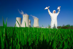 Man at nuclear power plant. Man in jumpsuit holding arrows at a nuclear power plant stock photo