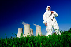 Man at nuclear power plant. A view of a man in a protective hazardous material suit, standing in front of a nuclear power plant, holding a white arrow stock photography