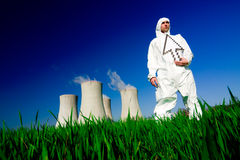 Man at nuclear power plant. A view of a man in a protective hazardous material suit, standing in front of a nuclear power plant, holding a white arrow royalty free stock image