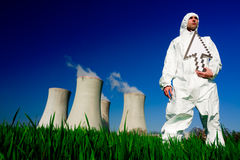 Man at nuclear power plant. A view of a man in a protective hazardous material suit, standing in front of a nuclear power plant, holding a white arrow stock photos