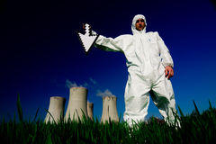 Man at nuclear power plant. A view of a man in a protective hazardous material suit, standing in front of a nuclear power plant, holding a white arrow stock image