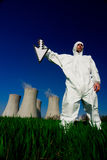 Man at nuclear power plant. A view of a man in a protective hazardous material suit, standing in front of a nuclear power plant, holding a white arrow royalty free stock photos