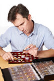 Man numismatist examines coin from the collection. Isolated Stock Photography