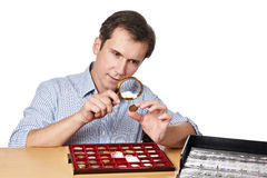 Man numismatist examines  coin with magnifying glass. Man numismatist examines with a magnifying glass coin from his collection isolated Royalty Free Stock Photos