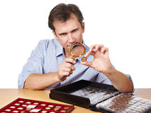 Man numismatist examines coin with magnifying glass. Man numismatist examines with a magnifying glass coin from his collection isolated Royalty Free Stock Photography