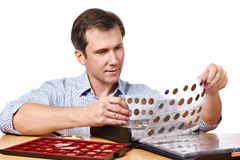 Man numismatist examines his collection of coin. Isolated Stock Images