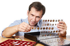 Man numismatist examines his collection of coin. Isolated Stock Photo