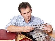 Man numismatist examines his collection of coin. Isolated Royalty Free Stock Images