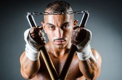 Man with the nunchucks against dark background Stock Images