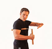 Man in with nunchucks. Man in martial arts concept with nunchucks on white royalty free stock image