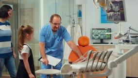 Man nurse inviting kid patient in consultation dental room
