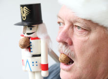 Man and nutcracker with walnuts Stock Images