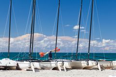 Man with oars goes on sea front. A lot of catamarans stay on the Royalty Free Stock Images