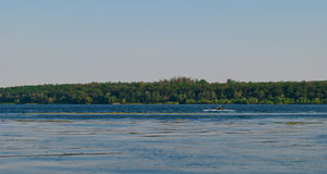 A man with oars sails in a canoe kayak boat on a river on a bright summer day against the backdrop of rocks and an island. Man in a cap sportsman with black oars Royalty Free Stock Photo