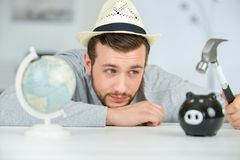 Man observes sadly before breaking piggy bank Stock Photo