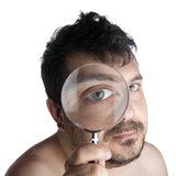 Man observing through a magnifying glass. Self portrait of a man looking though a magnifying glass royalty free stock image