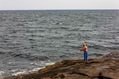 Man Ocean Fishing off the Rocks at Cape Neddick. Man Ocean fishing probably for Stripper fish. That is a type of ocean bass much prized for its fight a taste royalty free stock image