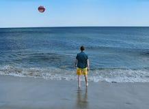 Man at ocean shore with beach ball Stock Photo