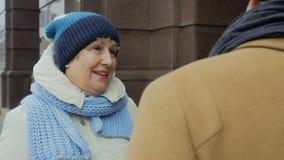 Man- och åldringkvinnasamtal utomhus lager videofilmer