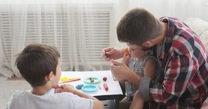 Man och barn som spelar med plasticine stock video