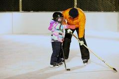 Man- och barnbindning, medan spela hockey Arkivfoto