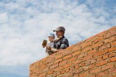 Man och barnpojke inom konstruktionsplats arkivbild